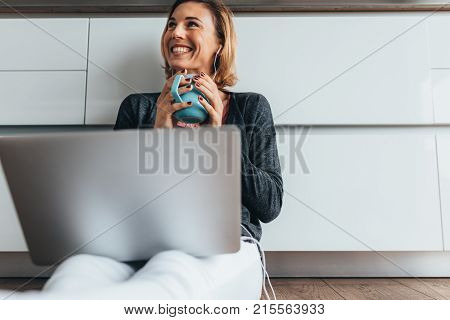 Woman Working On Laptop Computer At Home