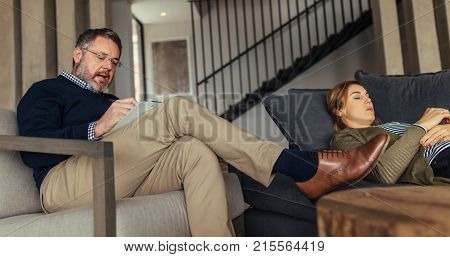 Female patient lying on sofa during psychotherapy session. Psychologist talking with woman during therapy.