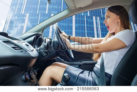 Young frightened driver woman squealing brakes. Shocked girl tooting horn in traffic jam
