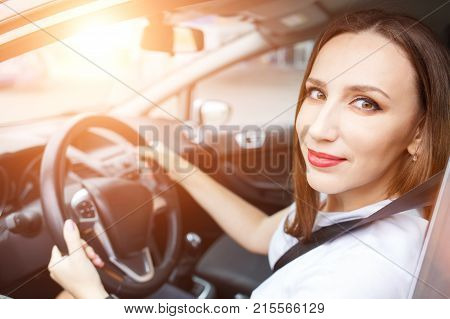 Young woman studying driving car in school. Happy hispanic girl steering wheel