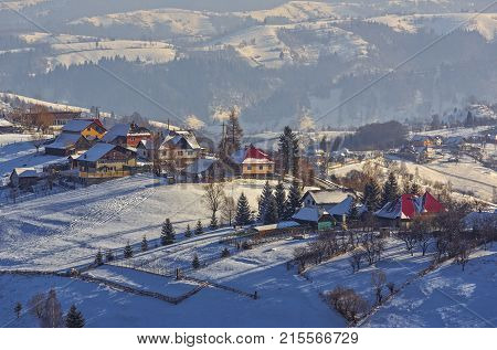 Countryside landscape with traditional Romanian village in the valleys of Bucegi mountains on a sunny cold winter morning in Pestera Brasov county Transylvania region Romania.