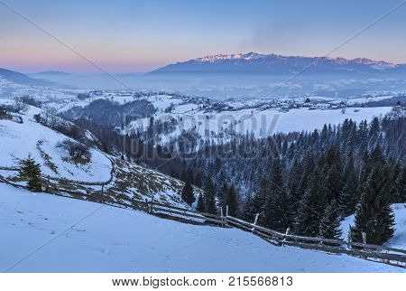 Picturesquet rural landscape with the snowy Rucar-Bran pass in the valley of Bucegi mountains at sunset Pestera village Brasov county Transylvania region Romania.