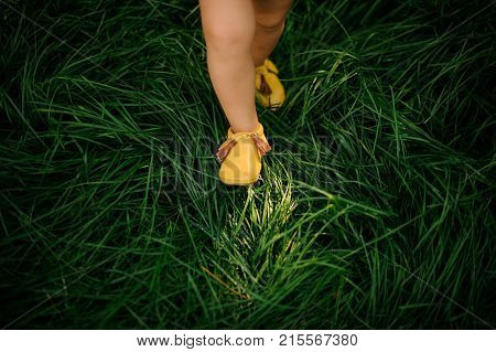 Cute little child legs shod in pretty yellow shoes walking on the fresh green grass