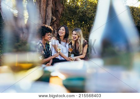 Three young women sitting outdoors with glass of wine and smiling. Multi-ethnic group of female friends having drinks together at party outdoors.