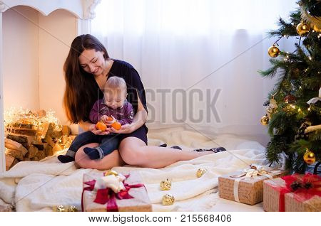 Mother with little cute baby boy in Christmas time with gifts and presents. Happy young mother with her sweet baby. Merry Christmas and Happy New Year. Baby first Christmas.