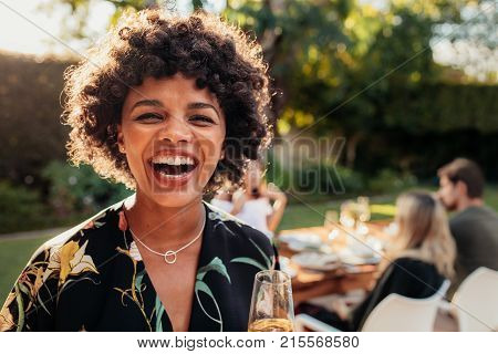 Laughing african woman with friends sitting in background at party. African woman enjoying at outdoors party.