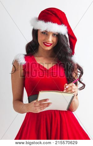 Pretty smiling pin-up Santa girl in red dress with wish list and pencil