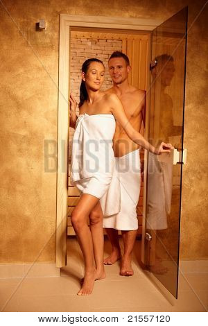 Happy couple standing at sauna door on healthy wellness program.?