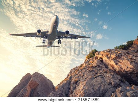 Big White Aircraft Is Flying Over Rocks At Sunset