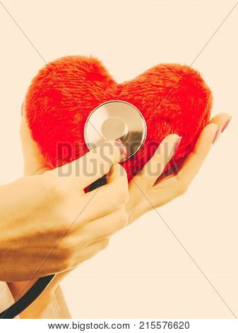 Medical examination of cardiology. Hands of cardiologist with heart and stethoscope. Female doctor makes measurement heartbeat. Filtered.