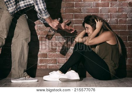 Man with bottle of alcohol abusing young woman against brick wall