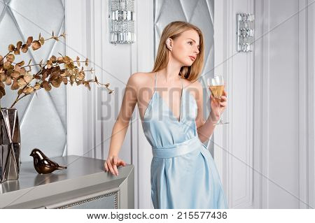 Elegant Blonde Lady With Glass Of Wine In Restaurant. Beautiful Sexy Young Woman With Long Hair Perf