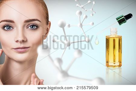 Cosmetic oil applying on face of young woman near big white molecule. Over blue background. poster
