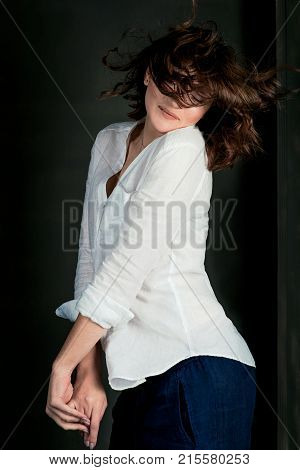 Portraite of young, beautiful smiling woman actress with short brown hair blowing by the wind in the studio