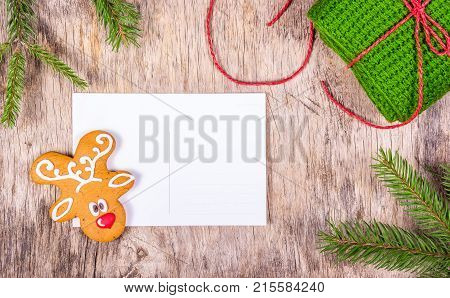 Christmas background with fir tree and blank greeting card. Preparing for Christmas. Painted gingerbread and knitted gift. Copy space