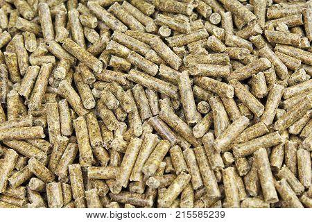 Granulated pet animal guinea pig hamster rabbit herb herbs food photo texture. Grass green plants as granulated pet food.