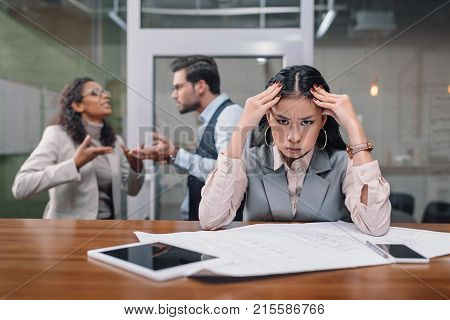 tired asian businesswoman working with paperwork while colleagues quarreling in office