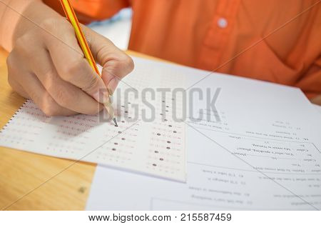 Students hands taking exams writing examination room with holding pencil on optical form of standardized test with answers and english paper sheet on row desk chair doing final exam in classroom.