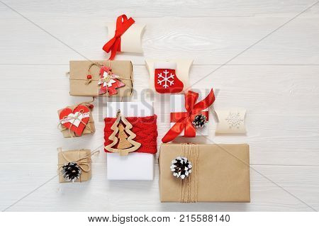 Mockup paper parcels wrapped tied with tags. A red heart and some christmas gift boxes wrapped with paper kraft and tied with red and white bakers twine on a white wooden table. Vintage Style.
