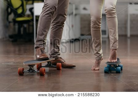 cropped view of businesspeople have fun with skateboards in office
