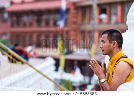 Kathmandu, Nepal - 06 October 2017: Middle-aged tibetian monk sincerely prays on the Boudhanath Stupa, Kathmandu, Nepal.