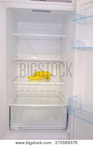 Bananas inside in empty clean refrigerator with opened door
