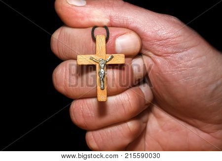 Hand with a cross on a dark background