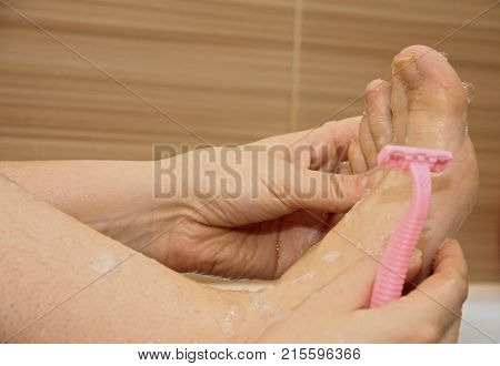 Woman shaving her legs sitting in the bathroom