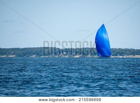 sailboat with bright blue spinnaker on Lake Michigan with sand dune coastline background