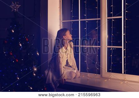 Cute Girl Teenager Sits On A Window Sill, Next To A Christmas Tree