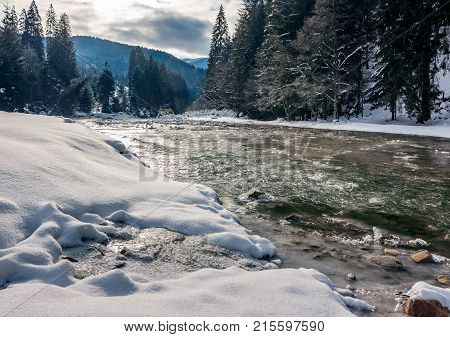 Cold Flow Of Forest River In Snowy Spruce Forest