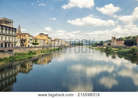Florence ITALY - july 11 2017: view of clouds reflected on Arno river and bridge Ponte di San Niccoló and historic buildings on banks of river on julyl 11 2017 in Florence Italy