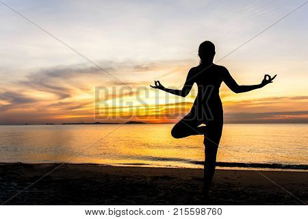 Meditation yoga lifestyle woman silhouette on the Sea sunset relax vital. Healthy Concept