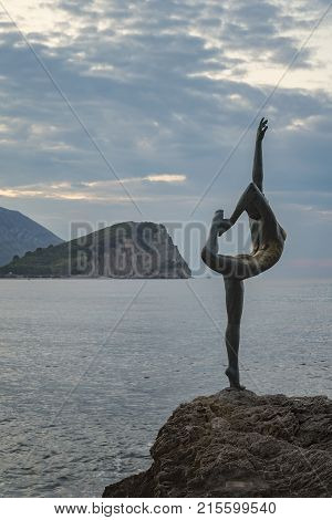 BUDVA MONTENEGRO - October 01 2017: Beautiful and elegant sculpture of a gymnast located on a rocky rock near the beach Morgen and the old town of Budva in Montenegro. It's often mistaken to be a ballet dancer.