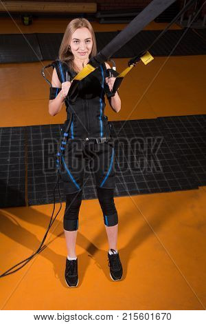 Blonde Girl In Electrical Muscular Stimulation Suit Doing Squat Exercise For Back And With Suspensio