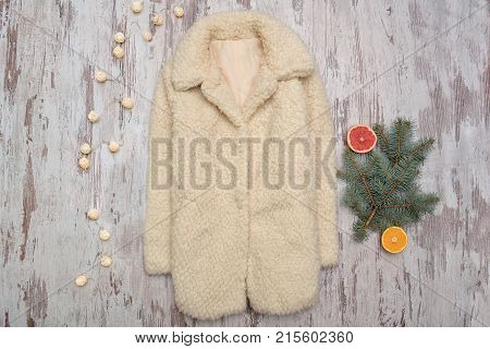 White Fur Coat And Fur-tree Branch On A Wooden Background. Fashionable Concept