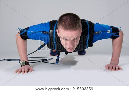 Man In An Electric Muscular Suit For Stimulation Does Push-up.