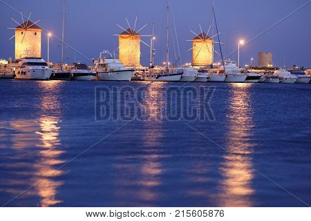 RHODES, GREECE - OCTOBER 10, 2017: Night view to windmills of Mandraki port. These three medieval windmills once ground the grains unloaded from merchant vessels in the harbor
