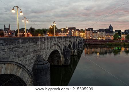 MAASTRICHT, NETHERLANDS - SEPTEMBER 7, 2013: Sint-Servaasbrug, the bridge of St. Servatius across the Meuse river in evening. Built in XIII century, it considered as the oldest Dutch bridge