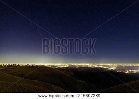 Night view panorama of a clear winter starry night sky; foreground the light of the cities along the Pianura Padana (like Milano and other big cities) in the Northern Italy.