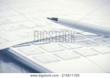Financial accounting Pen on calculator and balance sheets