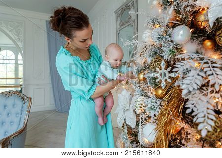 Happy family mother and daughter decorating Christmas tree on Christmas eve at home. Young mother holding her newborn child. Woman and new born girl relax in a white bedroom near the Christmas tree. Mother breast feeding baby. Family at home. Young mother