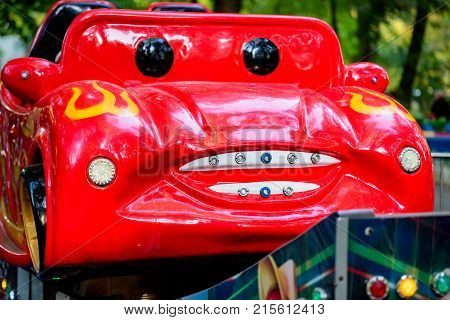 Close up empty bright red car with face painted on it in an amusement park