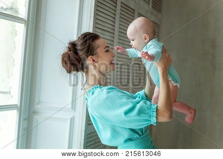 Mother holding her child. Young mother playing whith her daughter. Woman and new born girl relax at home. Mother breast feeding baby. Happy family at home. Young mother playing whith her newborn daughter