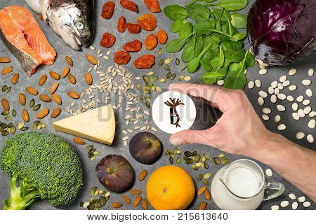 Food products useful for strengthening bones. Set of natural food products are sources of vitamins and minerals. Man's hand holds tag with homemade application from paper - symbol of strengthening bones. Top view