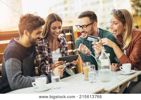Friends having a coffee together. Two women and two men at cafe shopping on line with digital tablet