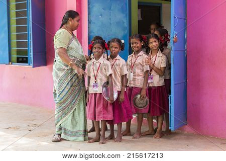 PONDICHERY PUDUCHERY INDIA - SEPTEMBER 04 2017. Unidentified boys children teacher go out from the classroom with their plates to have a lunch at the outdoor canteen.