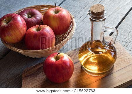A Bottle Of Apple Cider Vinegar With Apples In A Basket