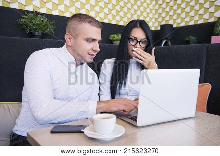 Business couple sitting in caffe and working on laptop
