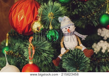 Kknitted snowman on a branch of a Christmas tree. nitted Chrismas toys on green fir branches